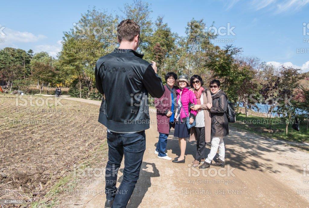 Man takes a group photo on Nami Island in South Korea stock photo