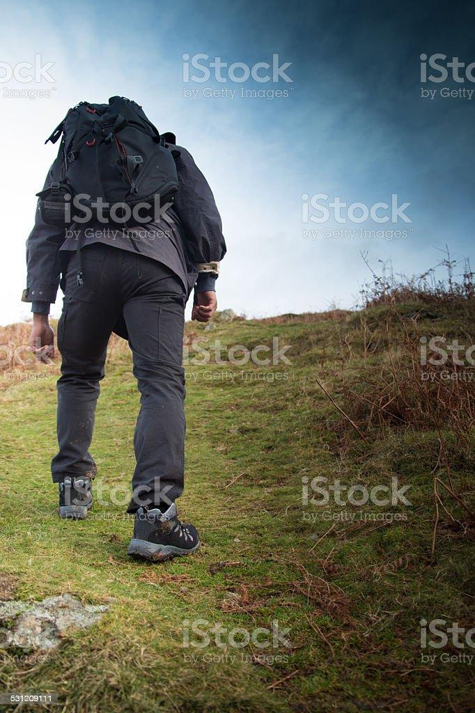 Man Takes A Hard Walk Up A Steep Hill stock photo