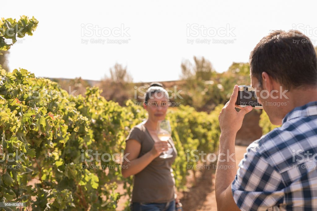 A man takes a photo of a woman in the winelands stock photo