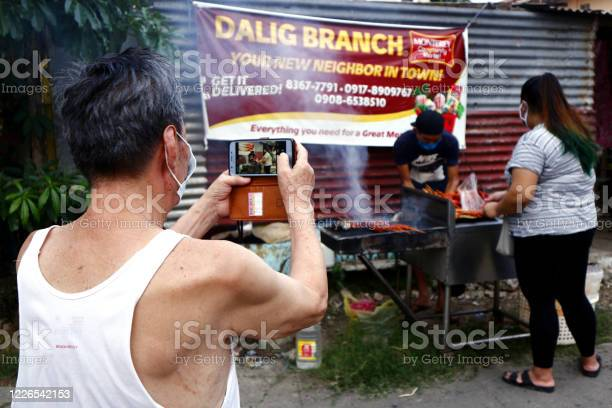 Man takes a photo with a smartphone of a vendor selling assorted picture id1226542153?b=1&k=6&m=1226542153&s=612x612&h=wvdhspf7kpl8sl rjp9glnnvr xeeiu rvixoxiub7q=