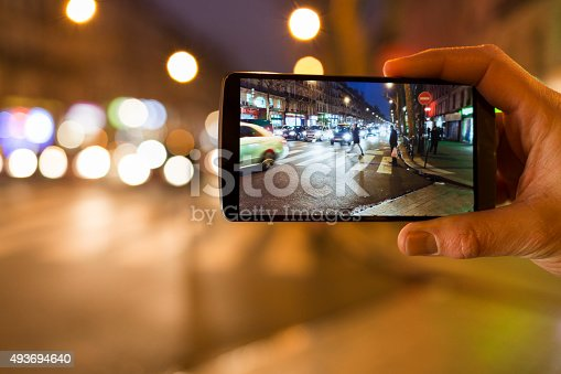 istock Man takes a picture in the street with mobile phone. 493694640