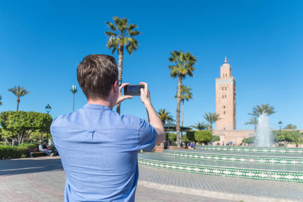 Man takes a smartphone photo of the Koutoubia Mosque in Marrakesh, Morocco stock photo