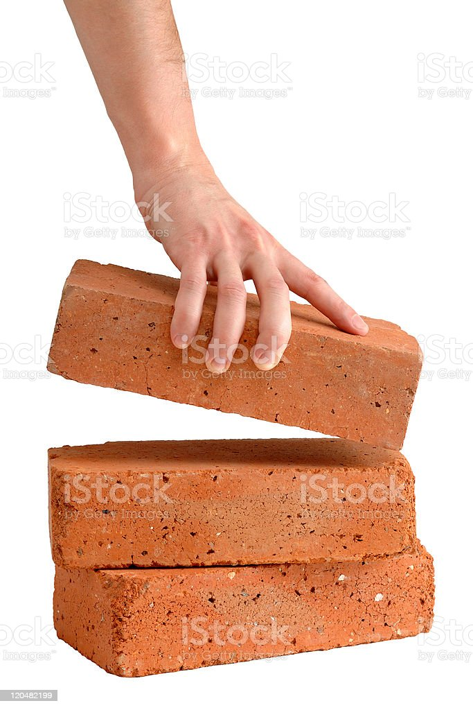 Man takes brick from the pile stock photo