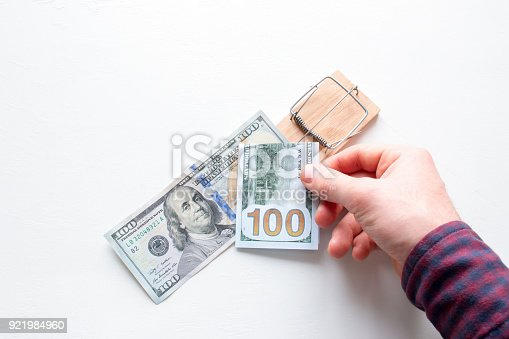 848170878istockphoto man takes money out of a mousetrap on a white background concept corruption 921984960
