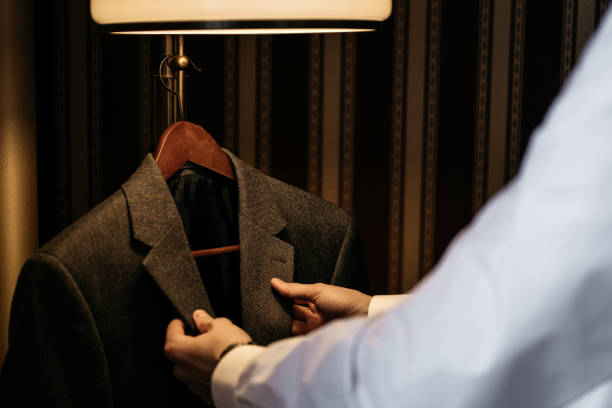 A man takes off his coat jacket, cropped image stock photo