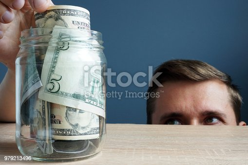 488389267istockphoto Man takes out the banknote from jar. Financial infidelity concept. 979213496