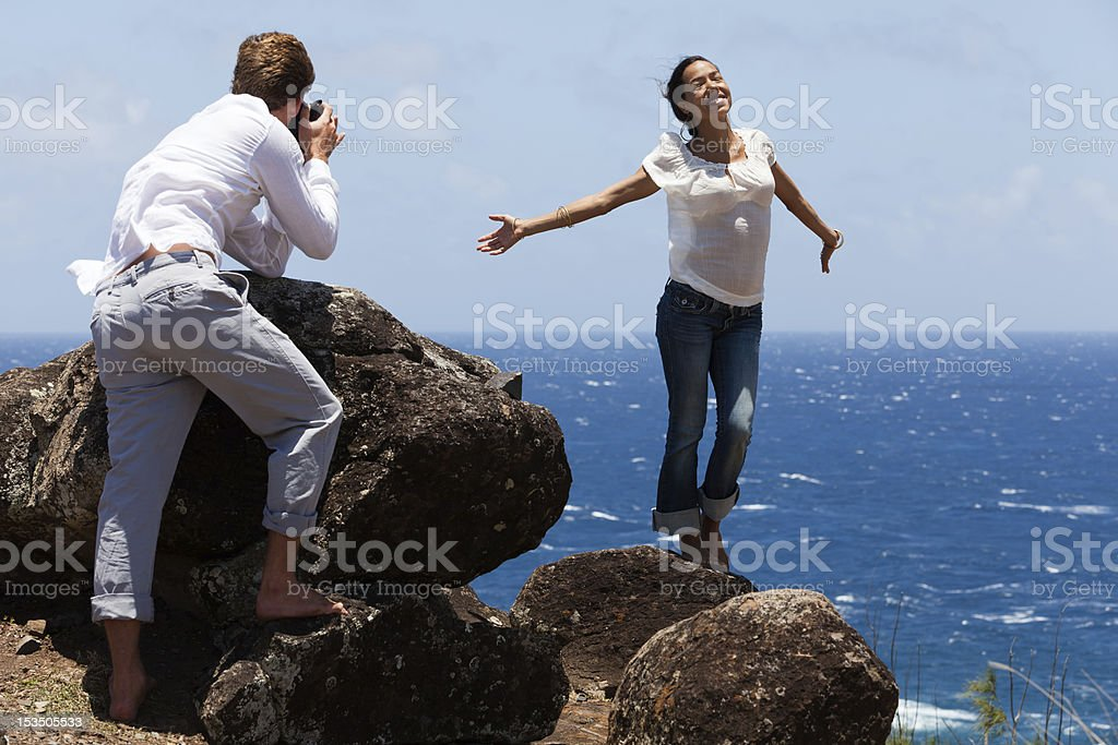 Man Takes Photo of Happy Woman on Hawaiian Cliffs stock photo