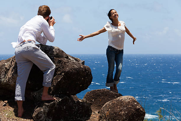 man takes photo of happy woman on hawaiian cliffs - carolinemaryan stock pictures, royalty-free photos & images