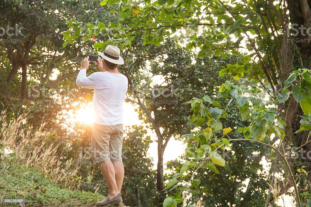 Hombre toma pic en jungle, usando sombrero en sunrise foto de stock libre de derechos
