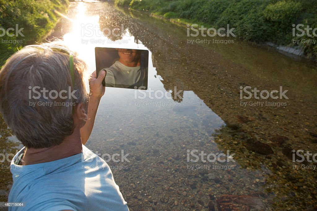 Man takes pic with digital tablet across pond stock photo