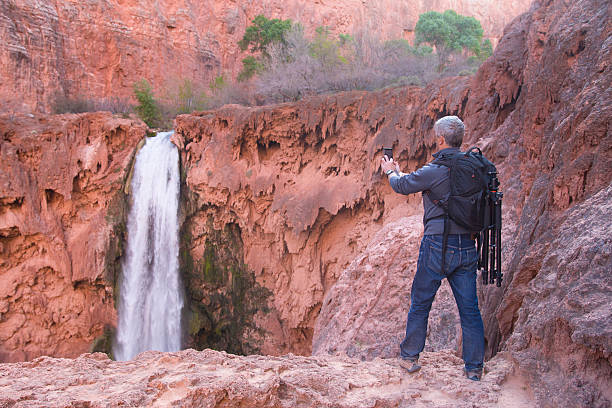 Man  takes picture of Mooney Falls with his mobil phone stock photo
