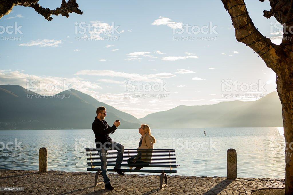 Man takes picture of woman on bench, lake edge stock photo