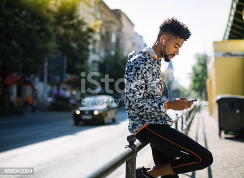 Side view of young man resting by city street and listening to music, taking a break after running session.