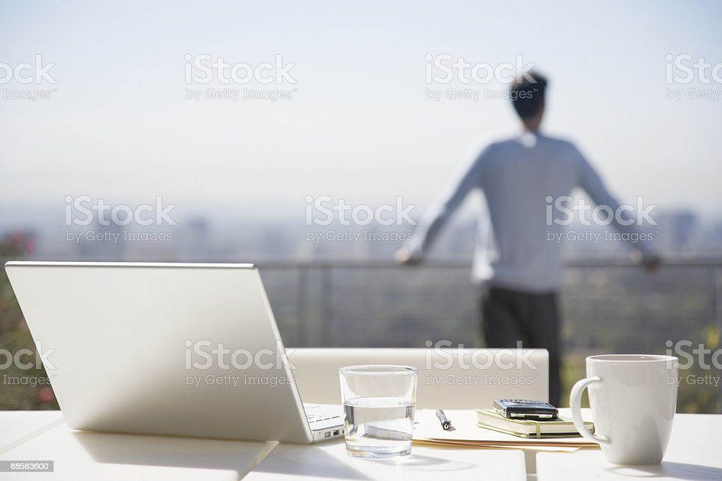 Man taking a break from working on balcony royalty-free stock photo