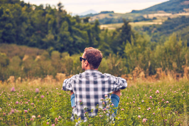 Man taking a break in nature and looking at the distant landscape. stock photo