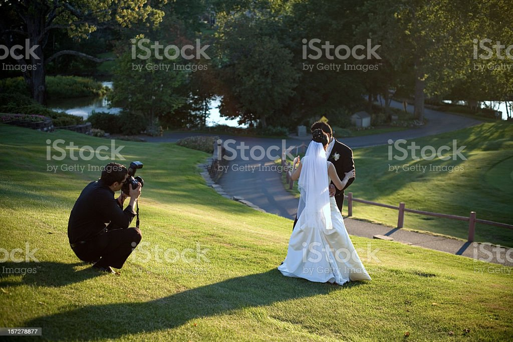 A man taking a photo of a bride and groom missing in grass royalty-free stock photo