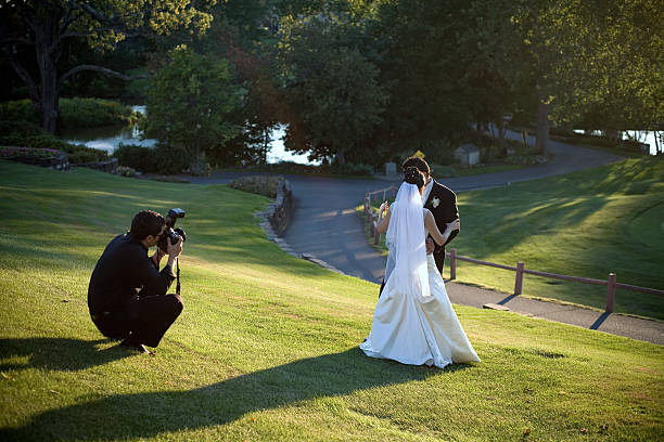 A man taking a photo of a bride and groom missing in grass stock photo