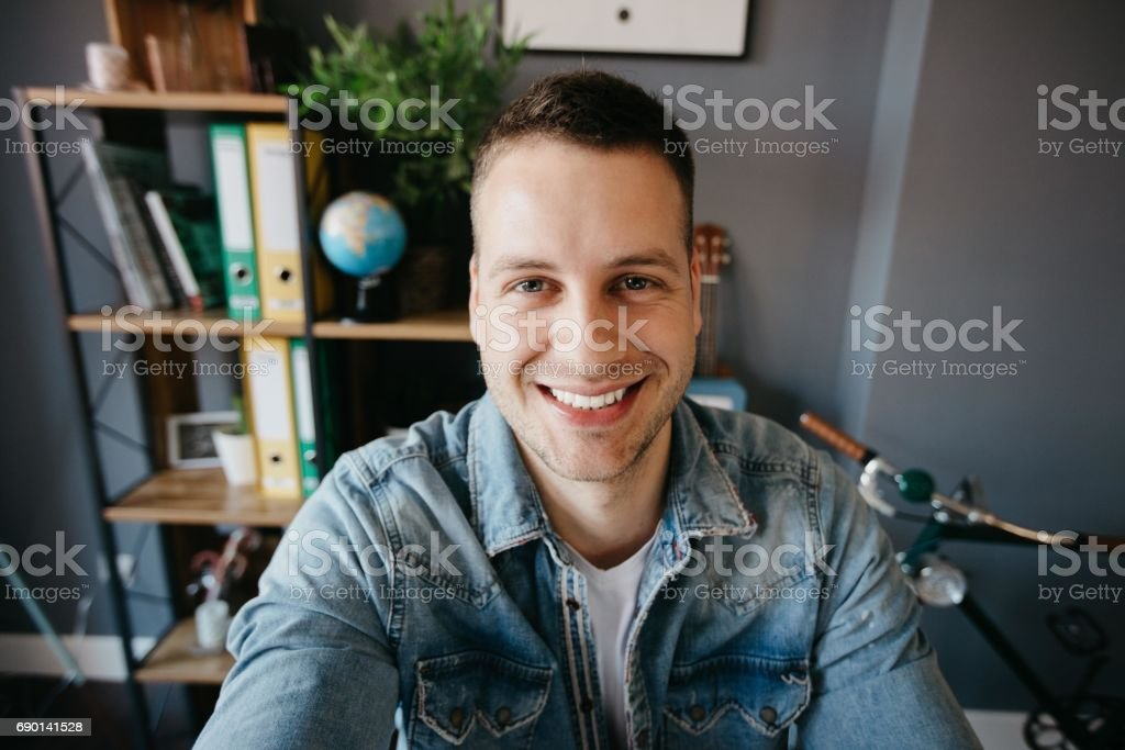 Man taking a photo of himself in the office stock photo