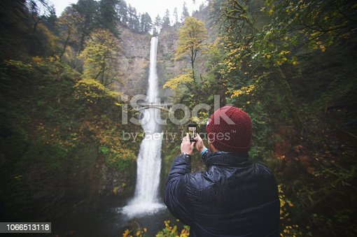A Caucasian male 40-44 years with a red beard taking photographing the Multnomah Falls Columbia River Gorge Portland Oregon USA in the rain