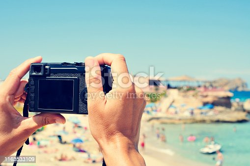 closeup of a young caucasian man taking a picture at Cala Conta beach in San Antonio, Ibiza Island, Spain