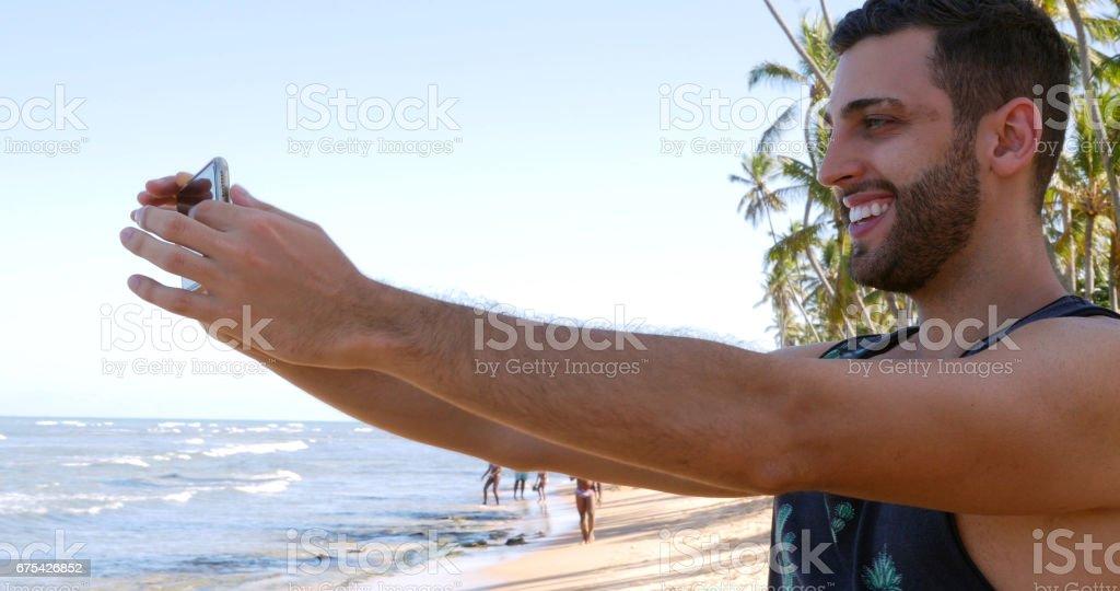 Tropikal bir plajda bir selfie alarak adam royalty-free stock photo