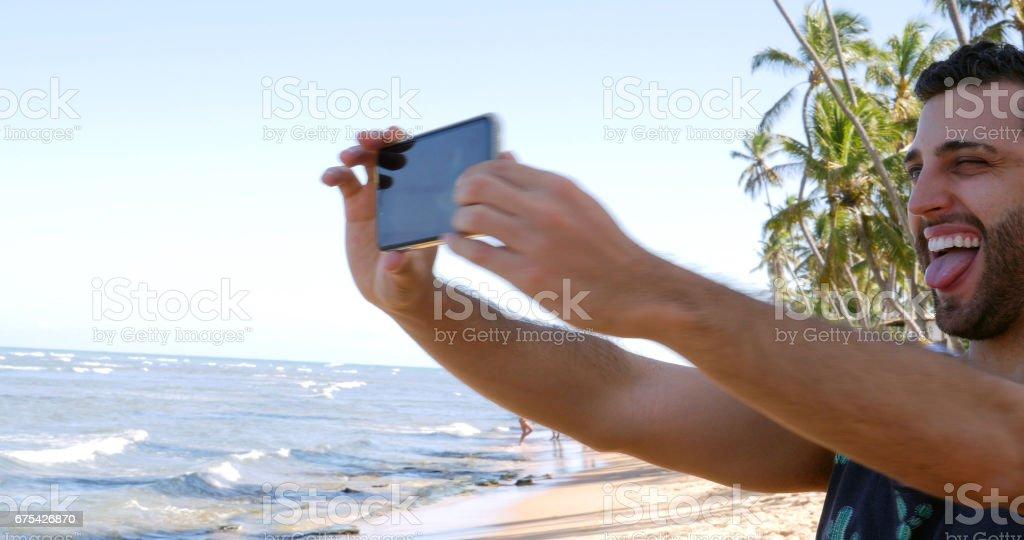 Homme tenant un selfie à Praia do Forte, Bahia, Brésil photo libre de droits