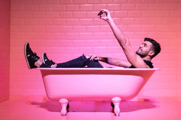 男子採取自拍在粉紅色的浴缸 - influencer 個照片及圖片檔