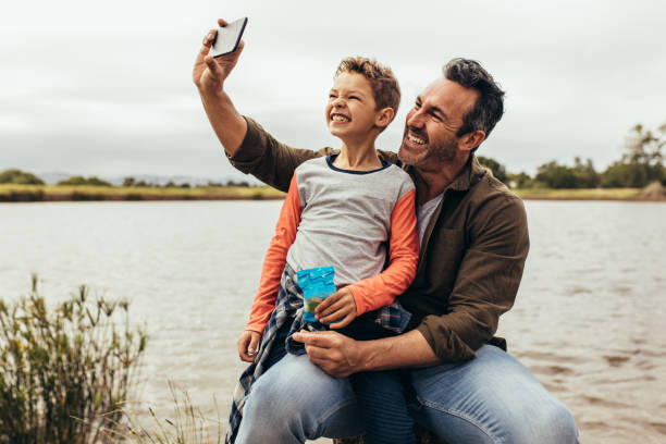 Man taking a selfie using a mobile phone Man taking a selfie with his son sitting near a lake. Smiling father and son having fun taking a selfie on a leisure trip to a lake. single father stock pictures, royalty-free photos & images