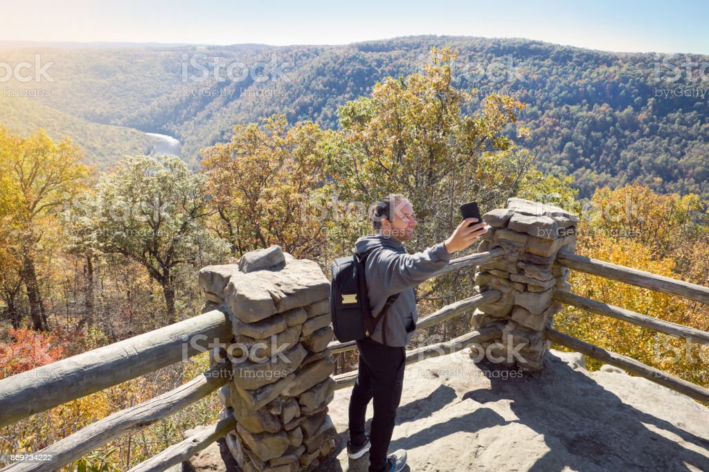 Man Taking A Selfie With Beautiful Fall Scene A man taking a selfie as he visits Coopers Rock State Forest in West Virginia, USA in the fall. 45-49 Years Stock Photo