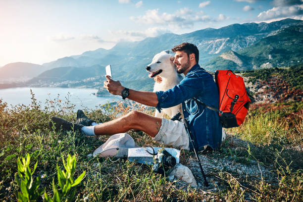 man taking a selfie with his best friend on top of the mountain stock photo