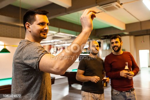 A man is aiming before taking a shot while playing darts in pool hall.