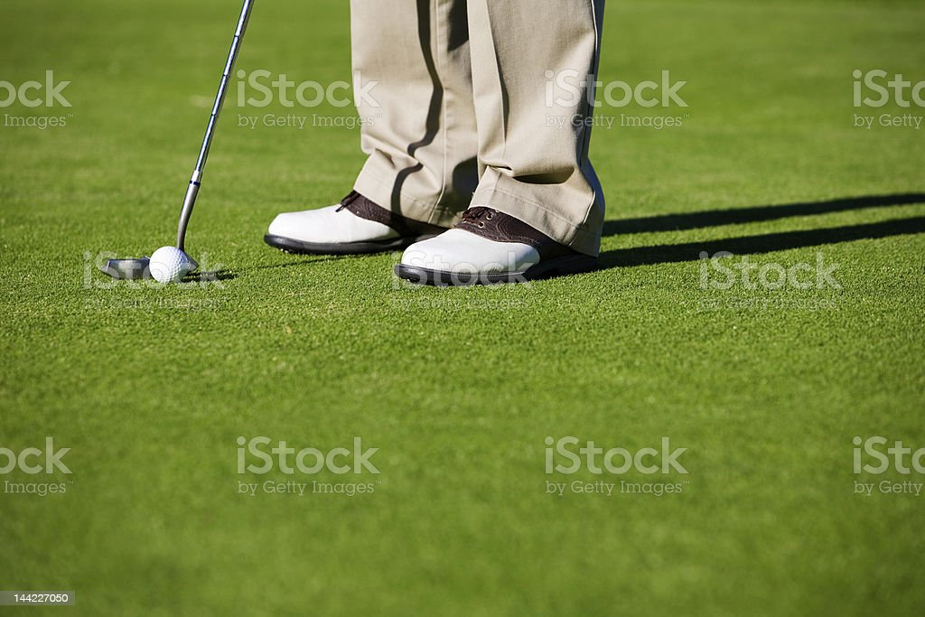 Man taking a swing with a putter on the green royalty-free stock photo