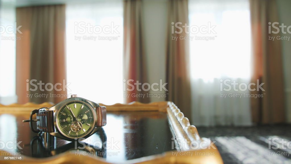 A Man Taking a Watch from the Table stock photo