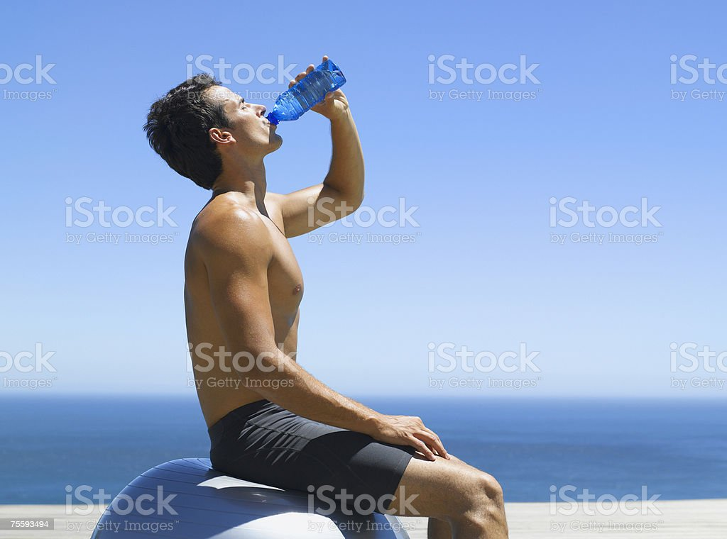 Man taking a water break sitting on an exercise ball royalty-free stock photo