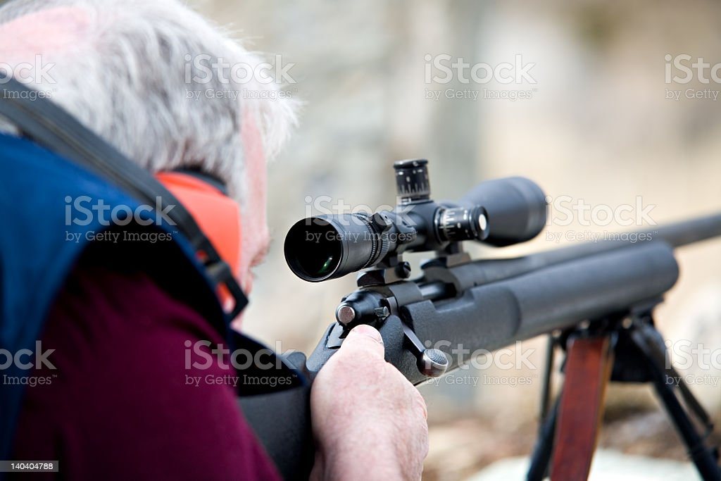 A man taking aim through the scope of a rifle stock photo