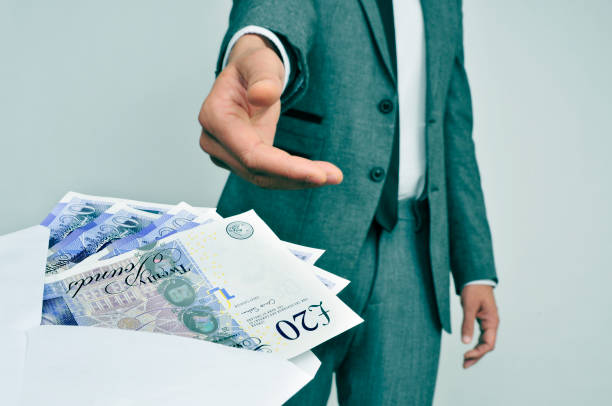 man taking an envelope full of pound sterling bills stock photo