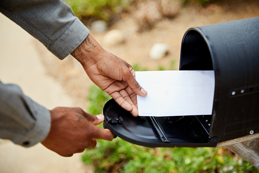 Closeup of a young African American man standing outside of his house and removing an envelope from his mailbox