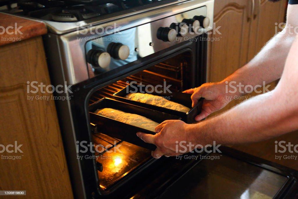 Hombre sacando pan al horno. Pan para hornear en casa - Foto de stock de 30-39 años libre de derechos
