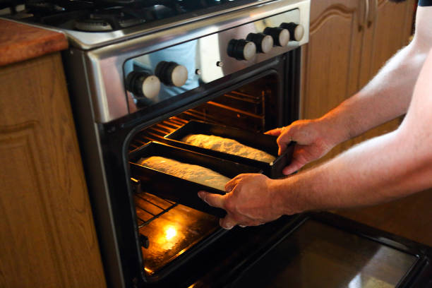 Man taking baked loafs of bread out of the oven. Baking bread at home stock photo