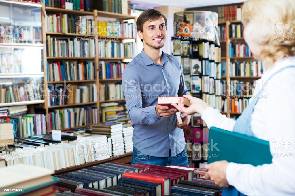 Man taking book from seller - foto de acervo