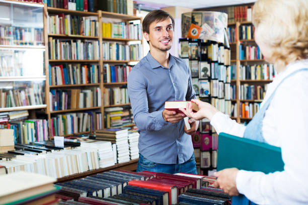 Man taking book from seller stock photo