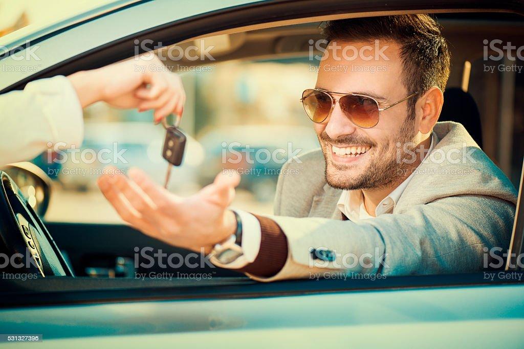 Man taking car key stock photo