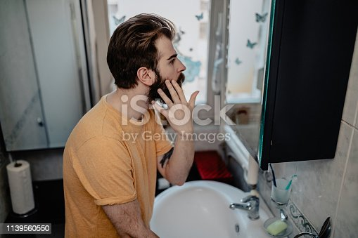 1134770826istockphoto Man taking care of his face in front of the mirror 1139560550