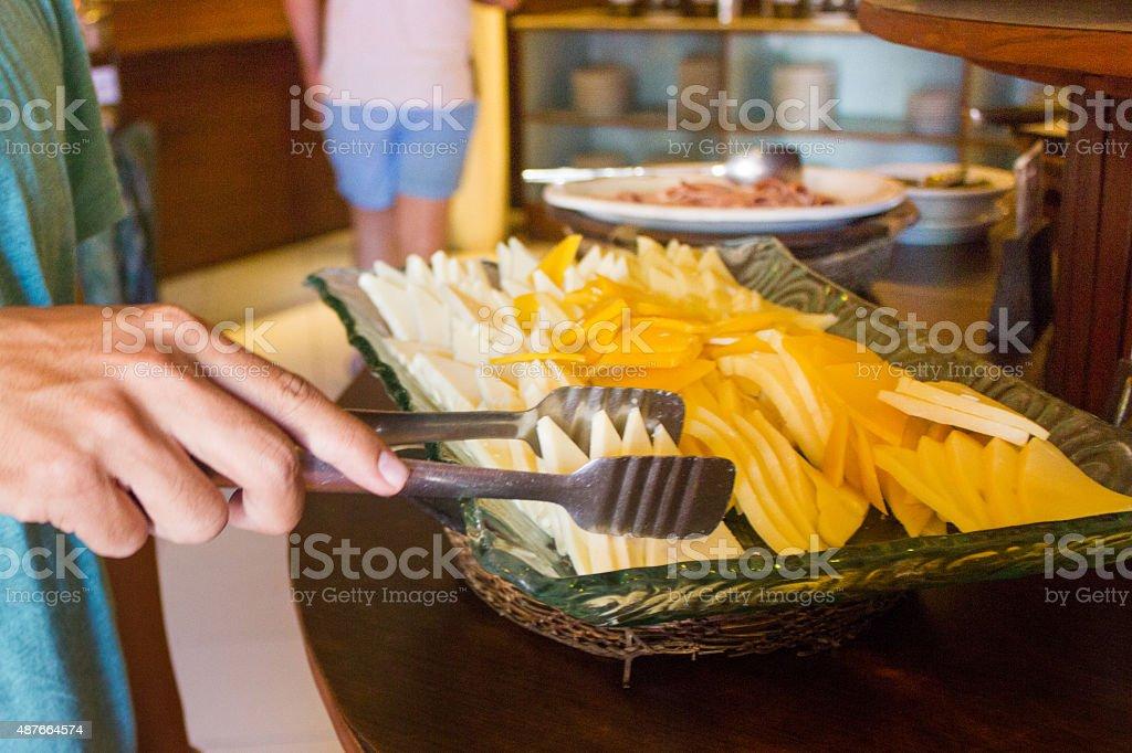 Man taking cheese on breakfast buffet stock photo