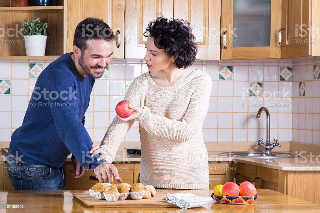 Man taking delicious cupcake while her woman offering him apple stock photo
