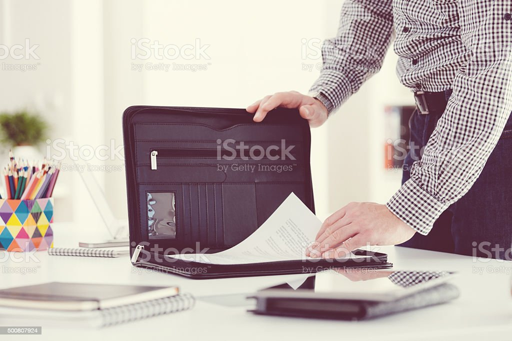 Man taking documents from briefcase, close up of hands stock photo
