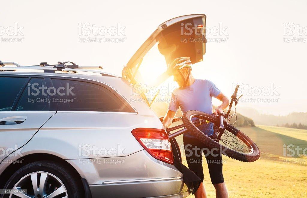 Mann sein Fahrrad herausnehmen aus dem Kofferraum eines Autos – Foto