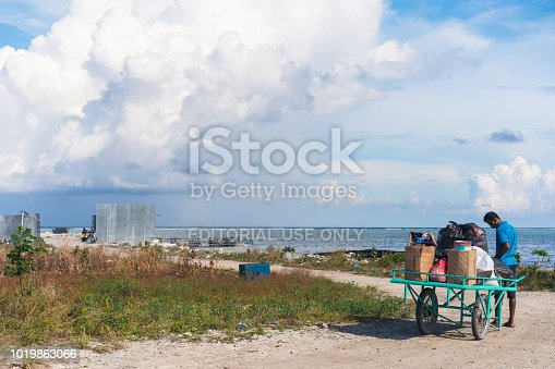 Maafushi Island, Maldives – April 10, 2018:  man puling his wagon with domestic, household waste to the to the waste collection side at Indian Ocean beach on one side of Maafushi island, Maldives. The wastes are exported to India but some of them, mostly plastics finish in see and surrounding beaches. It is part of growing tourist development on Maldives Islands. Maafushi is Kaafu Atoll, central point for traveling around the sandy islands, resorts