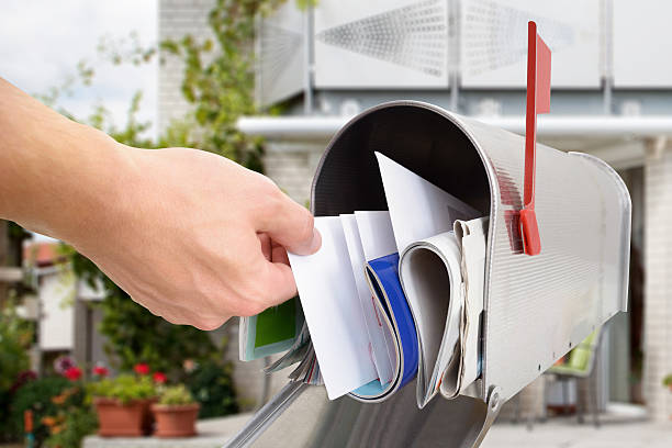 man taking letter from mailbox - mail stock photos and pictures