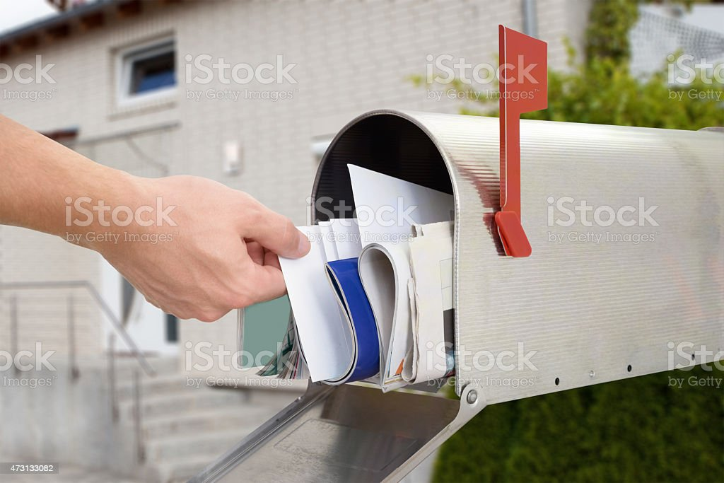 Man Taking Letter From Mailbox stock photo